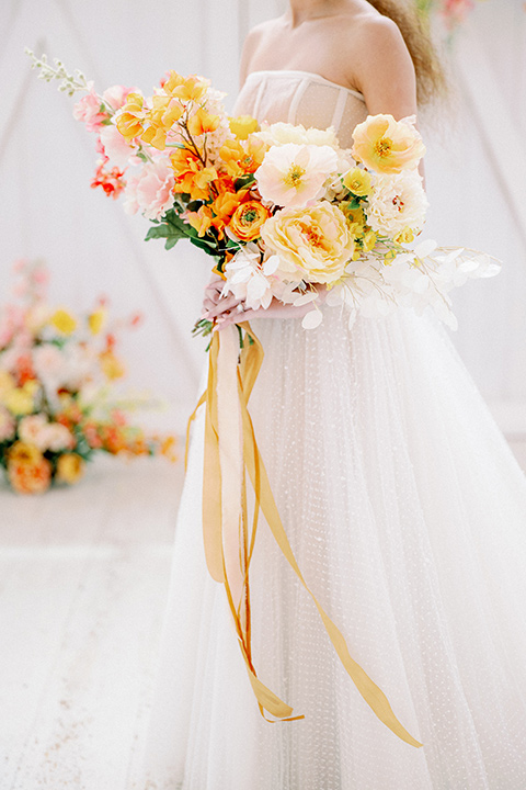 bride in a full tulle ballgown with a strapless design holding gold and orange flowers