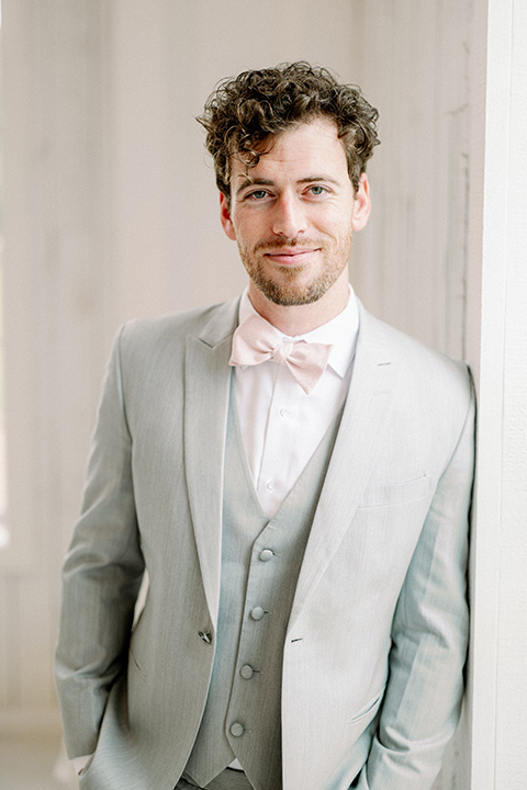 groom in a light grey suit with pink bow tie