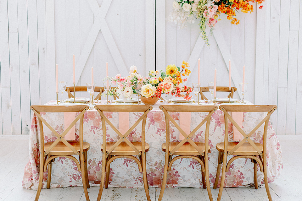 pink and white floral linen with gold charger plates and flatware and wooden chairs