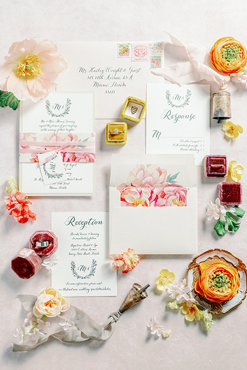 white invitations with a pink watercolor design