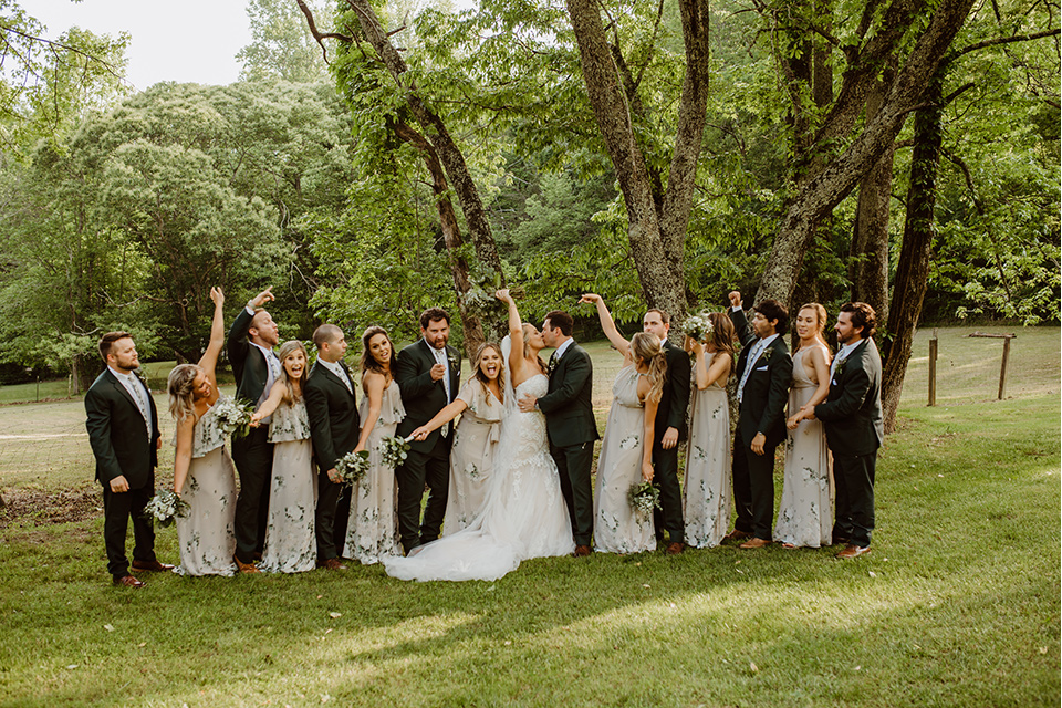 Horse-Range-Vista-bridal-party-hands-in-the-air-bridesmaids-in-sage-dresses-with-green-and-white-flowers-on-it-groomsmen-in-green-suits-with-floral-ties-bride-in-a-lace-mermaid-gown-with-a-long-veil-groom-in-a-green-suit-with-a-floral-tie