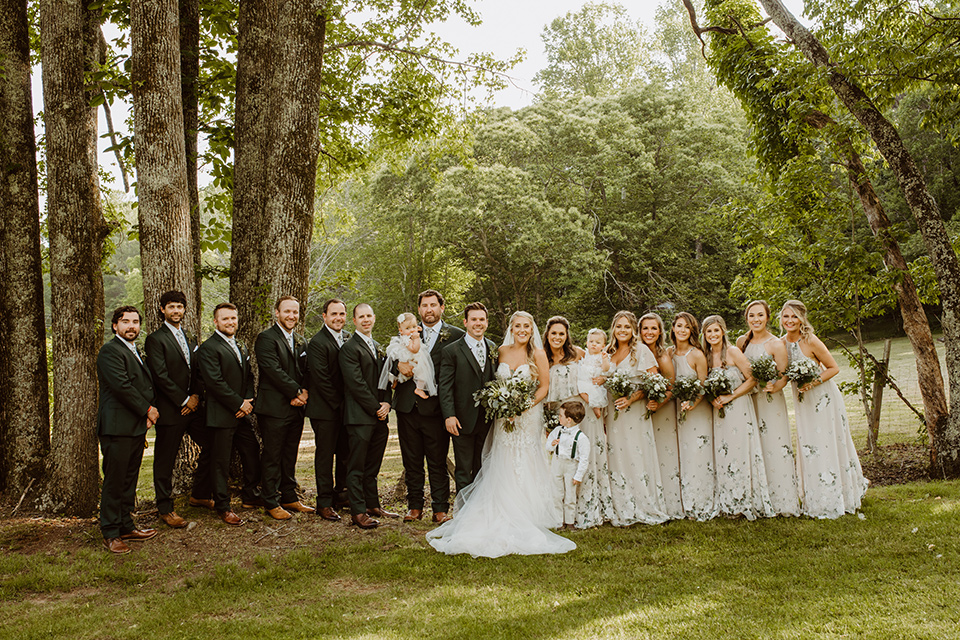 Horse-Range-Vista-bridal-party-standing-bridesmaids-in-sage-dresses-with-green-and-white-flowers-on-it-groomsmen-in-green-suits-with-floral-ties-bride-in-a-lace-mermaid-gown-with-a-long-veil-groom-in-a-green-suit-with-a-floral-tie