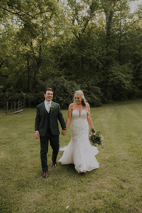 Horse-Range-Vista-bride-and-groom-walking-towards-camera-bride-in-a-lace-strapless-mermaid-gown-and-groom-in-a-green-suit-with-floral-tie
