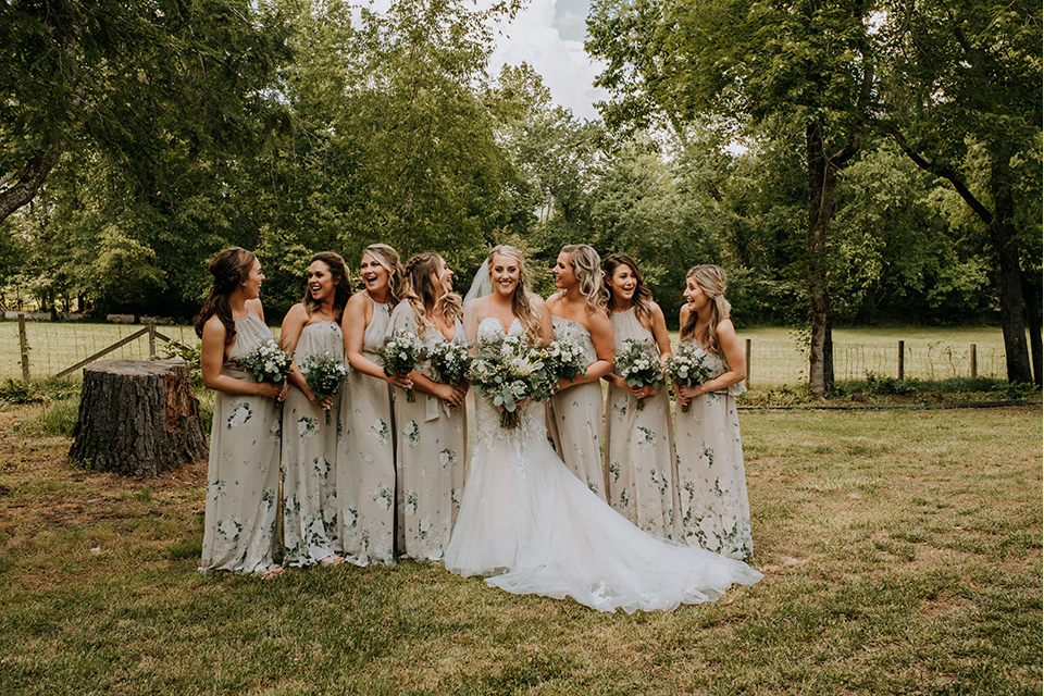 Horse-Range-Vista-bridesmaids-in-sage-dresses-with-green-and-white-flowers-on-it-bride-in-a-lace-mermaid-gown-with-a-long-veil