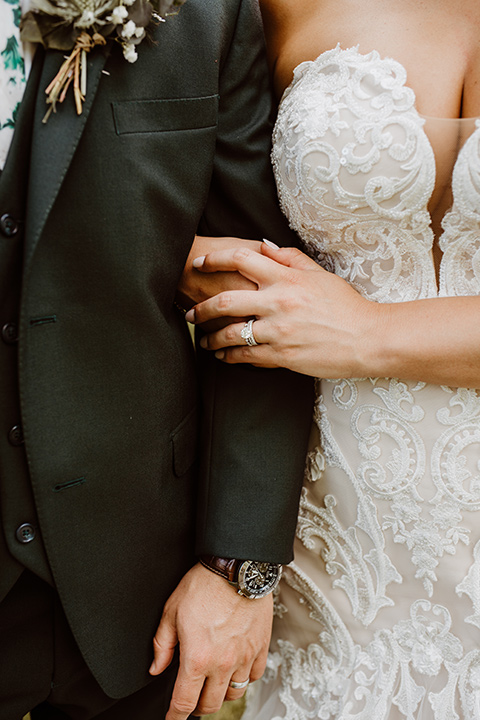Horse-Range-Vista-close-up-on-couples-attire-bride-in-a-lace-mermaid-gown-with-a-sweetheart-neckline-groom-in-a-green-suit-with-a-floral-tie