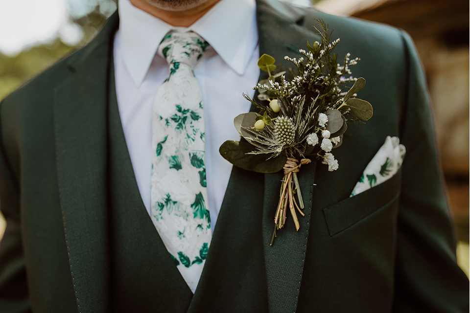 Horse-Range-Vista-close-up-on-groom-in-a-green-suit-with-a-floral-tie
