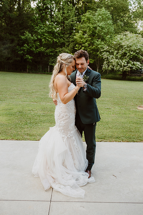 Horse-Range-Vista-couple-dancing-bride-in-a-lace-mermaid-gown-with-a-sweetheart-neckline-groom-in-a-green-suit-with-a-floral-tie