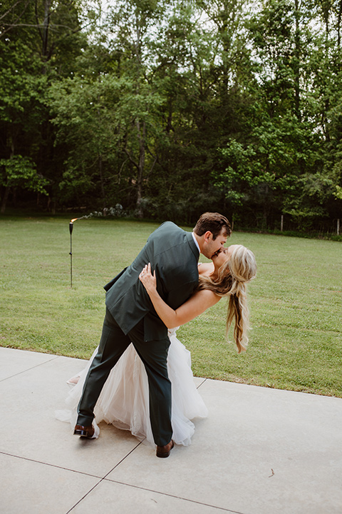 Horse-Range-Vista-couple-daning-at-reception-bride-in-a-lace-strapless-mermaid-gown-and-groom-in-a-green-suit-with-floral-tie