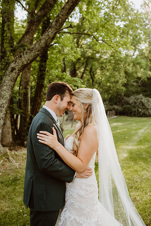 Horse-Range-Vista-couple-touching-heads-bride-in-a-lace-strapless-mermaid-gown-and-groom-in-a-green-suit-with-floral-tie