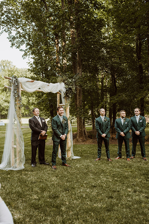 Horse-Range-Vista-groom-at-ceremony-in-a-green-suit-with-a-floral-tie