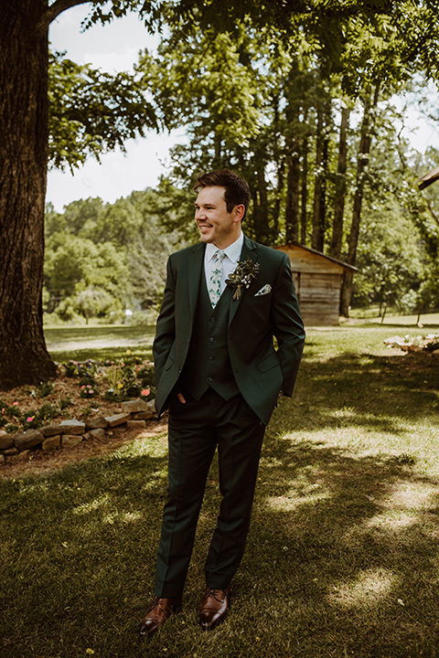 Horse-Range-Vista-groom-standing-by-tree-in-a-green-suit-with-a-floral-tie