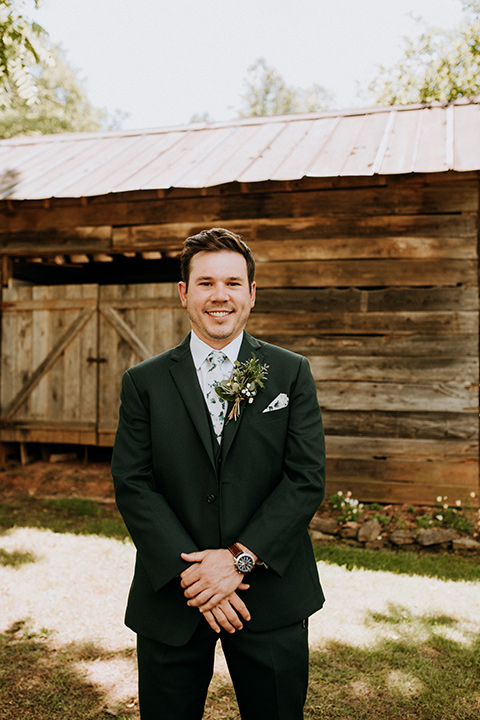 Horse-Range-Vista-groom-standing-in-a-green-suit-with-floral-tie