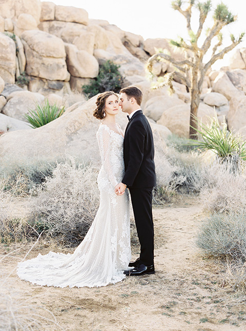 Desert-Lux-Shoot-bride-and-groom-close-together-bride-in-a-lace-form-fitting-gown-with-long-sleeves-and-a-high-neckline-the-groom-wears-a-black-tuxedo-with-a-black-bow-tie