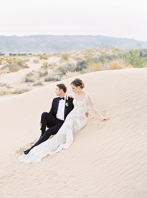 Desert-Lux-Shoot-bride-and-groom-in-the-sand-the-bride-is-in-a-long-lace-gown-with-long-sleeves-and-a-high-neckline-the-groom-is-in-a-black-tuxedo-and-black-bow-tie