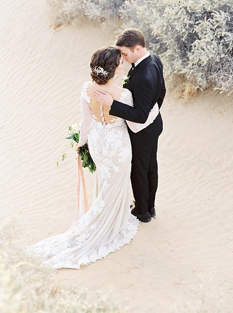 Desert-Lux-Shoot-bride-and-groom-kissing-bride-in-a-lace-form-fitting-gown-with-long-sleeves-and-a-high-neckline-the-groom-wears-a-black-tuxedo-with-a-black-bow-tie
