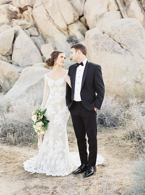 Desert-Lux-Shoot-bride-and-groom-looking-at-each-other-bride-in-a-lace-form-fitting-gown-with-long-sleeves-and-a-high-neckline-the-groom-wears-a-black-tuxedo-with-a-black-bow-tie
