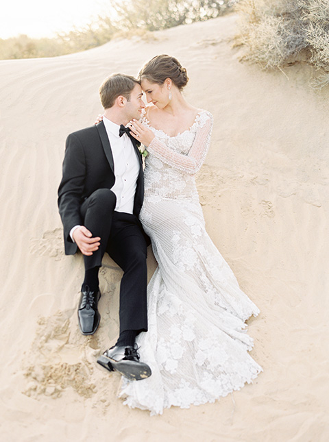 Desert-Lux-Shoot-bride-and-groom-sitting-the-bride-is-in-a-long-lace-gown-with-long-sleeves-and-a-high-neckline-the-groom-is-in-a-black-tuxedo-and-black-bow-tie