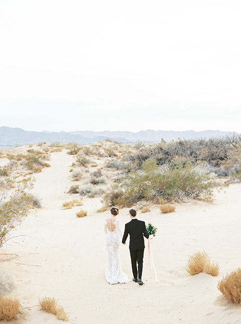 Desert-Lux-Shoot-bride-and-groom-walking-away-bride-in-a-lace-form-fitting-gown-with-long-sleeves-and-a-high-neckline-the-groom-wears-a-black-tuxedo-with-a-black-bow-tie