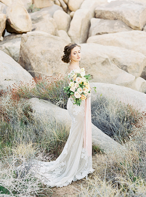 Desert-Lux-Shoot-bride-looking-over-her-shoulder-bride-in-a-lace-form-fitting-gown-with-long-sleeves-and-a-high