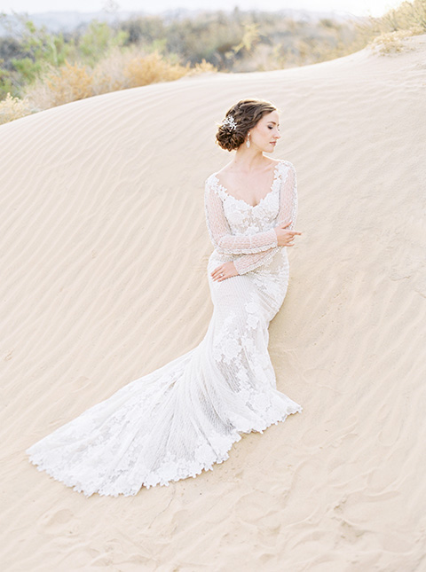 Desert-Lux-Shoot-bride-standing-the-bride-is-in-a-long-lace-gown-with-long-sleeves-and-a-high-neckline