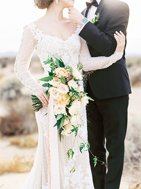 Desert-Lux-Shoot-close-up-on-briode-and-groom-attire-the-bride-is-in-a-long-lace-gown-with-long-sleeves-and-a-high-neckline-the-groom-is-in-a-black-tuxedo-and-black-bow-tie