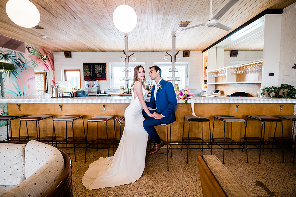 bride and groom at the bar at the drifter hotel, bride is in a formfitting gown with straps and her hair down in a loose style while the groom is in a cobalt blue suit with brown shoes and his shirt undone