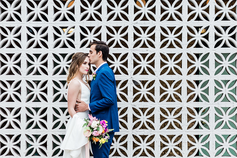 bride and groom outside the venue next to a cinder block wall, bride is in a formfitting gown with straps and her hair down in a loose style while the groom is in a cobalt blue suit with brown shoes and his shirt undone