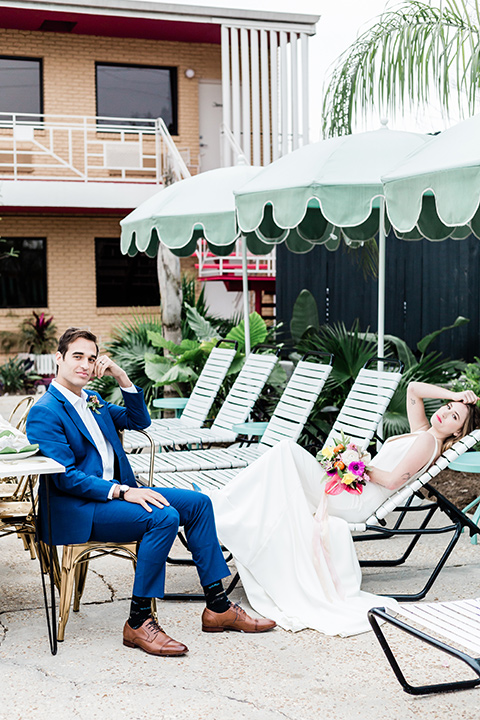 bride and groom on the poolside furniture, bride is in a formfitting gown with straps and her hair down in a loose style, while the groom is in a cobalt blue suit with brown shoes and his shirt undone