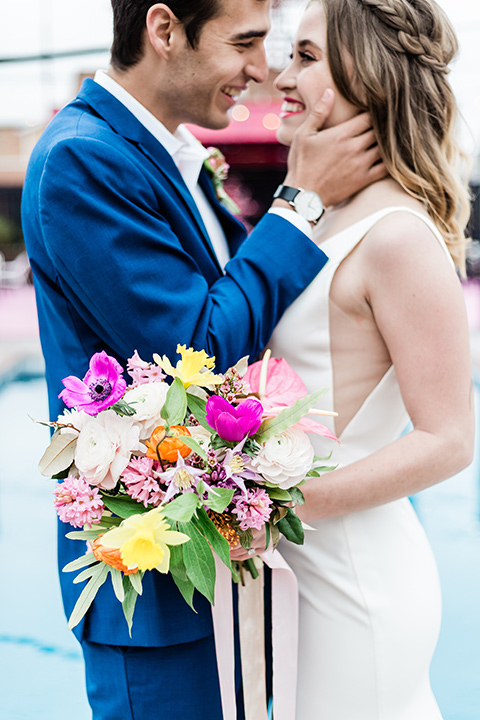 bride and groom close up by the pool, bride is in a formfitting gown with straps and her hair down in a loose style and holding a bright colored bouquet of flowers, while the groom is in a cobalt blue suit with brown shoes and his shirt undone