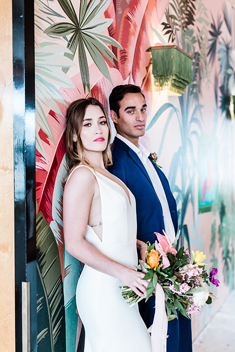 bride and groom standing by a mural, bride is in a formfitting gown with straps and her hair down in a loose style and holding a bright colored bouquet of flowers, while the groom is in a cobalt blue suit with brown shoes and his shirt undone