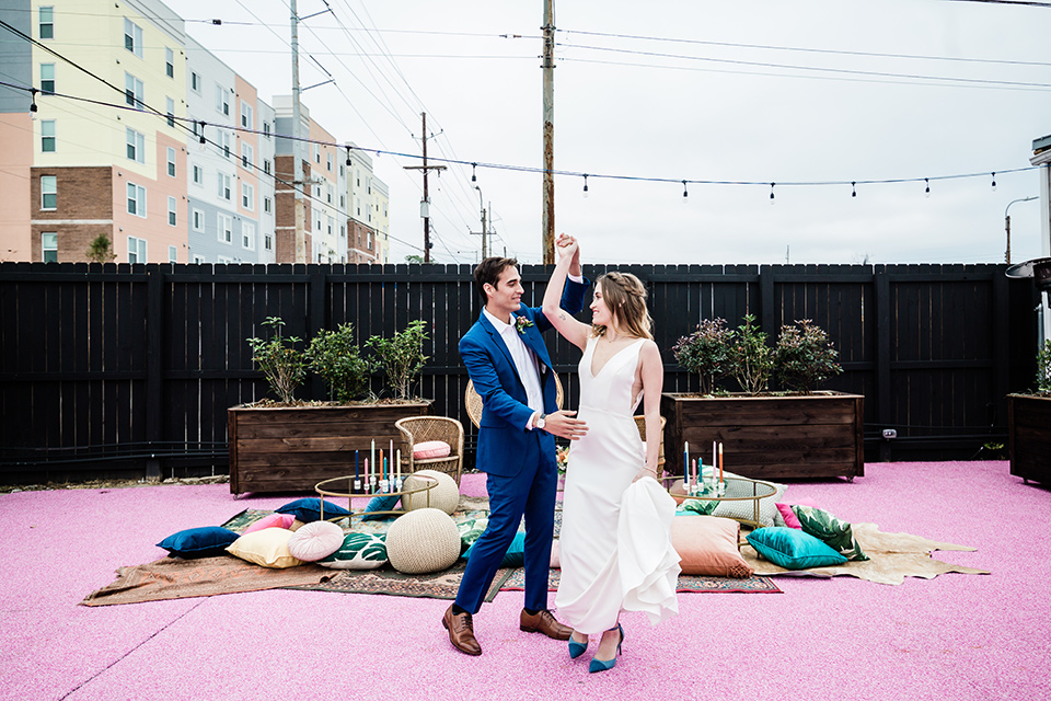 bride and groom dancing, bride is in a formfitting gown with straps and her hair down in a loose style while the groom is in a cobalt blue suit with brown shoes and his shirt undone