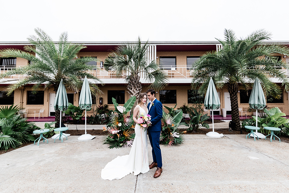 bride and groom standing close outside the hotel, bride is in a formfitting gown with straps and her hair down in a loose style while the groom is in a cobalt blue suit with brown shoes and his shirt undone
