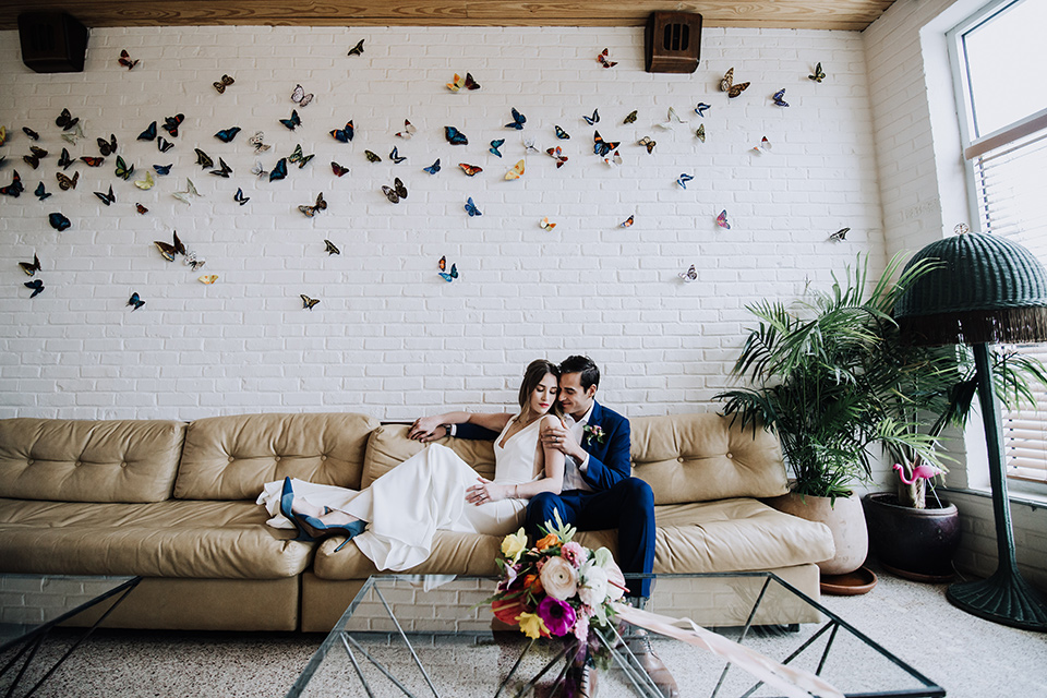 bride and groom on the couch with a butterfly art piece above them, bride is in a formfitting gown with straps and her hair down in a loose style while the groom is in a cobalt blue suit with brown shoes and his shirt undone