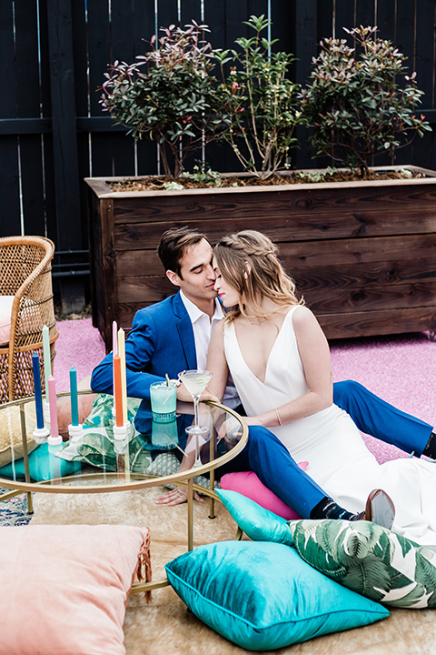bride and groom sitting on outside furniture pillows, bride is in a formfitting gown with straps and her hair down in a loose style and holding a bright colored bouquet of flowers, while the groom is in a cobalt blue suit with brown shoes and his shirt undone