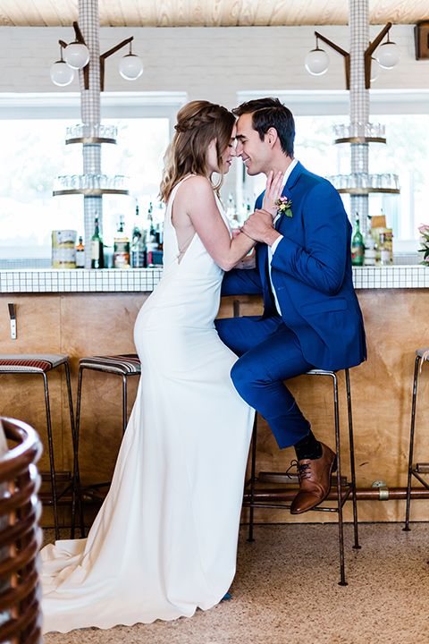 bride and groom sitting at bar, bride is in a formfitting gown with straps and her hair down in a loose style, while the groom is in a cobalt blue suit with brown shoes and his shirt undone