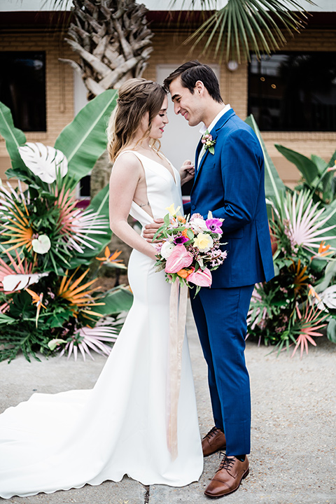 bride and groom standing with their heads touching, bride is in a formfitting gown with straps and her hair down in a loose style, while the groom is in a cobalt blue suit with brown shoes and his shirt undone