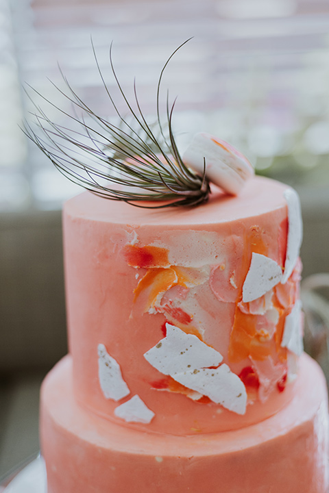coral colored cake with gold and white designs on it