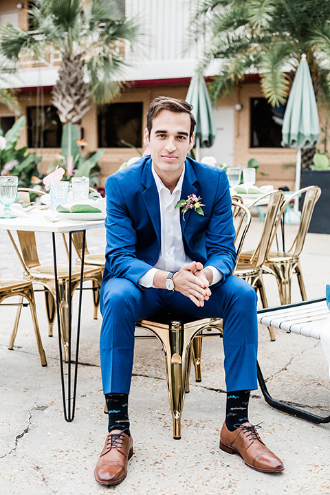 the groom is in a cobalt blue suit with brown shoes and his shirt undone sitting next to the pool