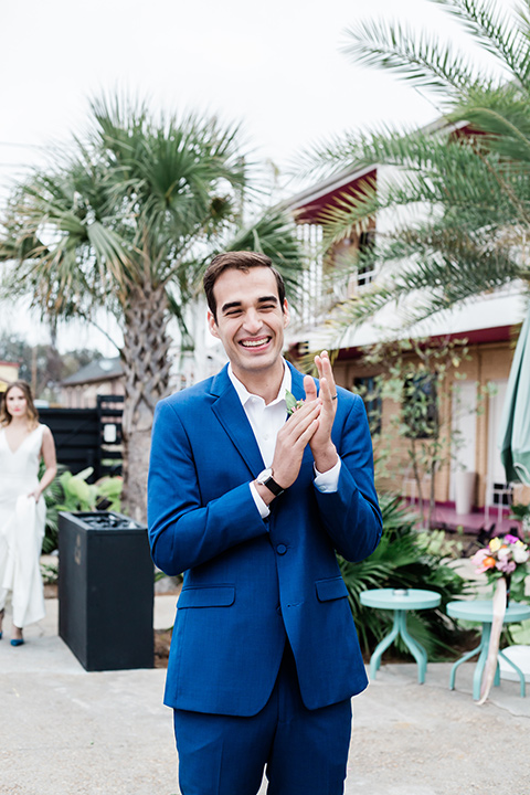 groom is in a cobalt blue suit with brown shoes and his shirt undone
