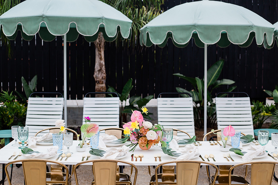 table set up with gold metal farm chairs and mint colored parasols over the table