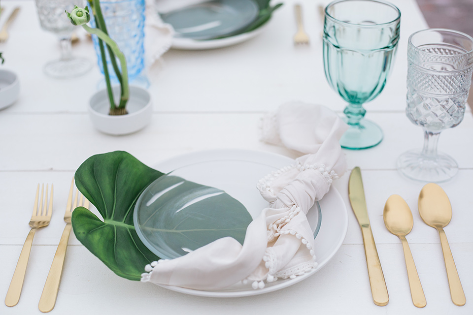 table flatware in gold with a white linen and a palm leaf as decor