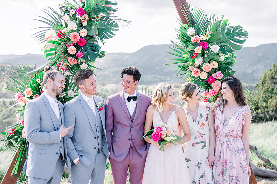 emerald-peak-temecula-wedding-bridal-party-bridesmaids-in-floral-gowns-groomsmen-in-light-blue-suits-bride-in-a-blush-toned-ballgown-with-straps-and-groom-in-rose-pink-suit