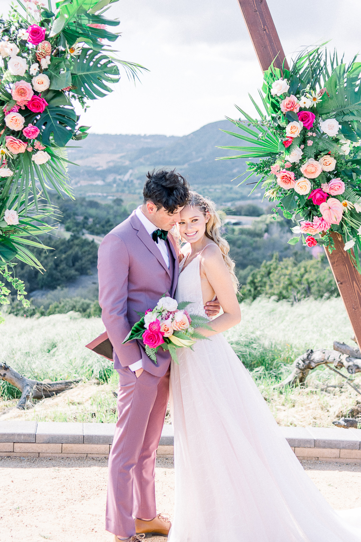 emerald-peak-temecula-wedding-bride-and-groom-ceremony-bride-in-a-blush-tulle-gown-with-straps-groom-in-a-rose-pink-suit-with-a-green-velvet-bow-tie