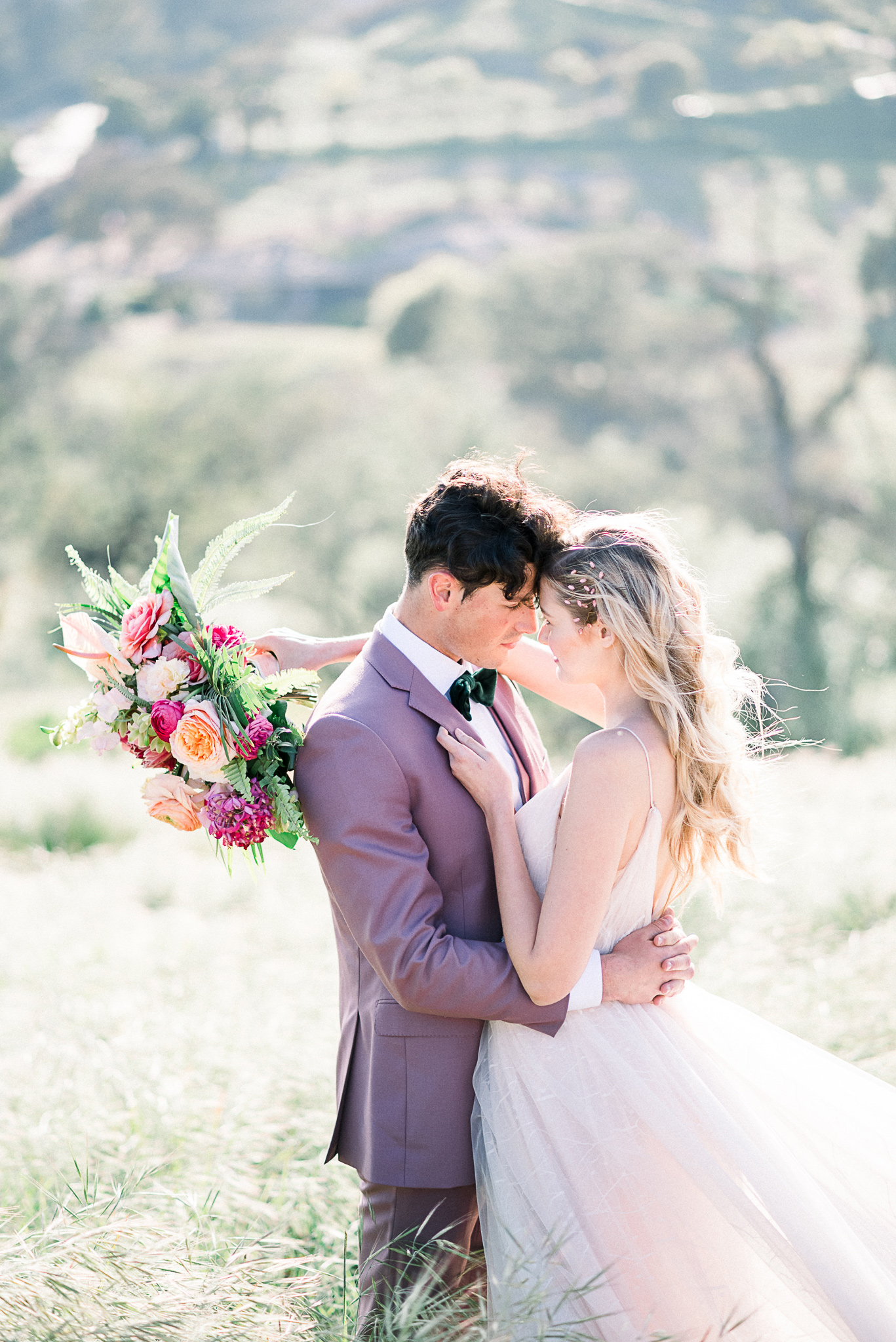 emerald-peak-temecula-wedding-bride-and-groom-touching-heads-bride-in-a-blush-tulle-gown-with-straps-groom-in-a-rose-pink-suit-with-a-green-velvet-bow-tie