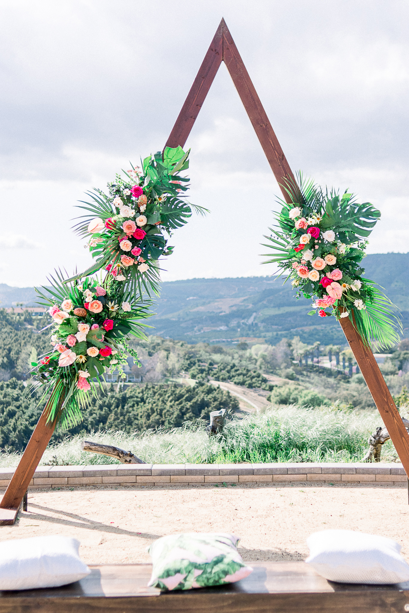 emerald-peak-temecula-wedding-ceremony-arch-in-a-deep-red-wood-in-a-triangle-shape-with-flowers-on-it