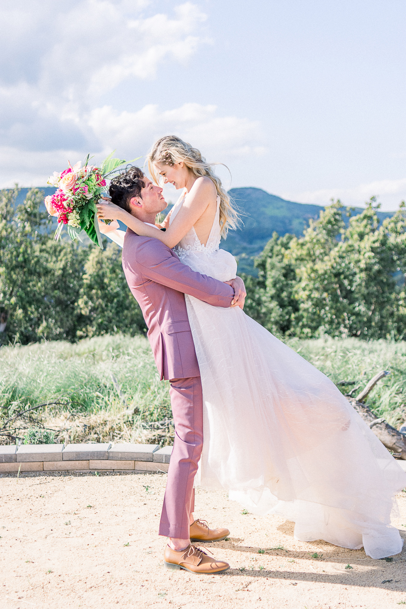 emerald-peak-temecula-wedding-groom-holding-up-bride-bride-in-a-blush-toned-tulle-ballgown-with-straps-groom-in-a-rose-pink-suit-with-a-green-velvet-bow-tie