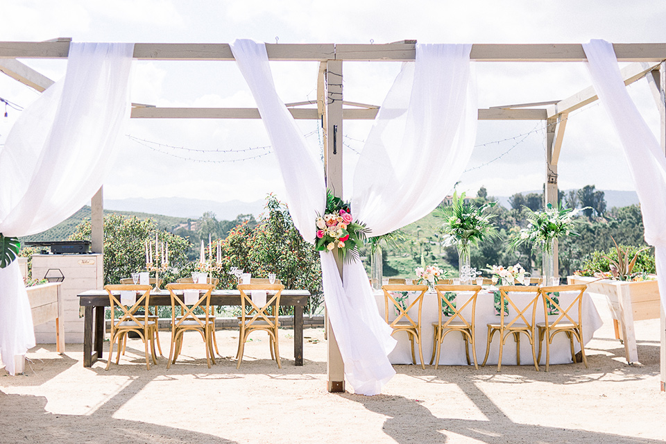 emerald-peak-temecula-wedding-reception-set-up-with-wooden-table-and-chairs-with-flowing-white-linens-around