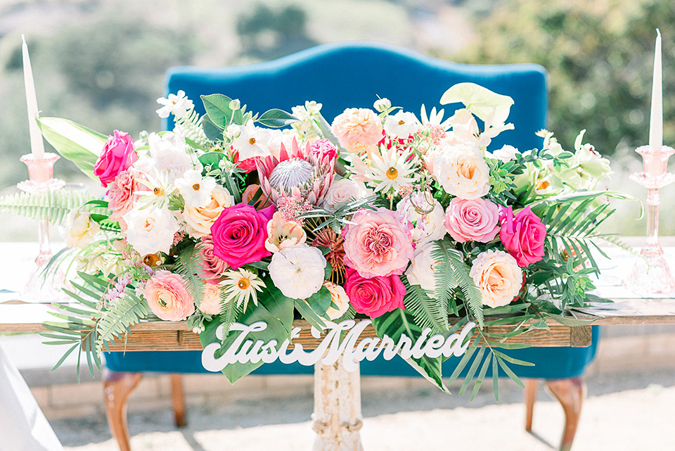 emerald-peak-temecula-wedding-sweetheart-table-with-a-blue-velvet-couch-and-bright-pink-flowers