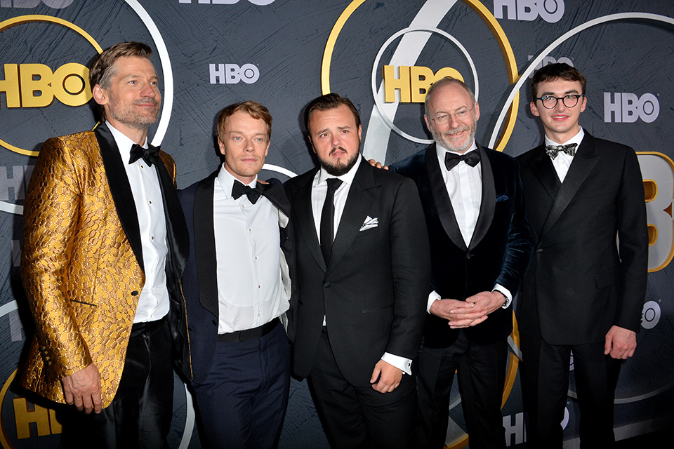 the game of thrones cast leading men all posing with each other, Nikolaj wearing a gold tuxedo coat the others wearing perfectly tailored black tuxedos and accessories