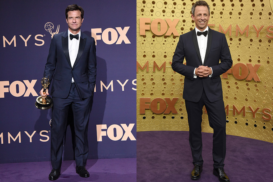 Jason Bateman wearing a navy blue tuxedo with a black peak lapel design and a black bow tie and Seth Meyers wearing a navy blue tuxedo with a black shawl lapel and black bow tie